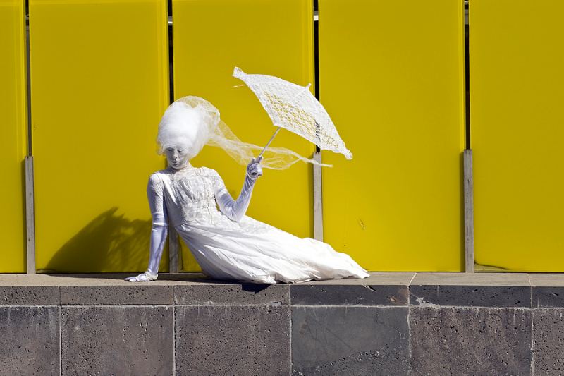 white-lady-by-yellow-wall